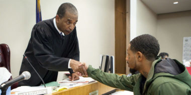 BUFFALO, NY - OCTOBER 23: Judge Robert Russell, creator of the Buffalo Veterans Treatment Court, shakes hands with veteran Justin Smith who has succeeded in his court, on October 23, 2012 in Buffalo, New York. The Buffalo Veterans Treatment Court started in January 2008 as a hybrid drug and mental health treatment court to provide judicially monitored treatment to war veterans in the criminal justice system. Vets appearing here struggle with substance addiction or serious mental health disease often accompanied by PTSD. The court provides lots of support to veterans in trouble to help them succeed. (Photo by Melanie Stetson Freeman/The Christian Science Monitor via Getty Images)
